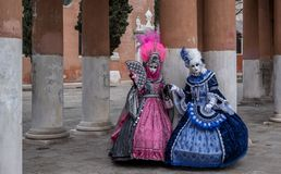 Two women in masks and ornate blue and pink costumes at Venice Carnival. Two women in masks and ornate blue and pink costumes standing in front of pillars at a Stock Images