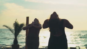 Two women meditating on the beach slow motion. Two women meditating on the beach stock video