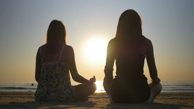 Two women meditating on a shore of the sea. Two women meditating on the shore of the sea stock footage