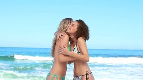 Two women meet up at the beach. And hug one another stock video footage