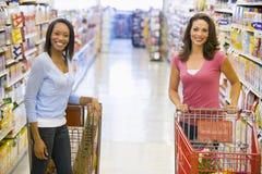 Two women meeting in supermarket