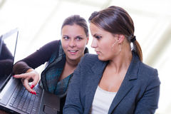 Two women in a meeting. Young beautiful girls working together Stock Photos