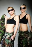 Two women in military clothes, army girls. Two women in military clothes and sunglasses army girls on gray background Royalty Free Stock Photo
