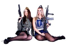 Two women in the military uniform with guns Stock Photos