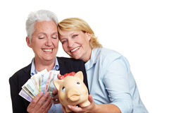 Two women with money and piggy bank Royalty Free Stock Image