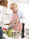 Two Women cooking In The Kitchen Stock Images