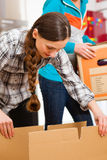 Two women with moving box in her house royalty free stock image