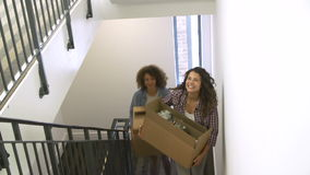 Two Women Moving Into New Home Carrying Box Upstairs. Two Women carrying boxes up stairs as they move into new home.Shot on Sony FS700 in PAL format at a frame stock video