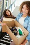 Two Women Moving Into New Home Carrying Box Upstairs. Two Women Moving Into New Home Carrying Box With Clothes In Upstairs Looking Happy royalty free stock photo