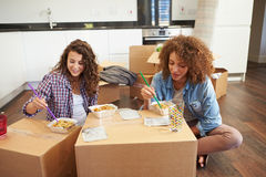 Two Women Moving Into New Home Enjoying Takeaway Meal. On Cardboard Boxes Sitting On Floor stock images