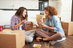 Two Women Moving Into New Home Enjoying Takeaway Meal. Sitting On Floor Laughing royalty free stock photography