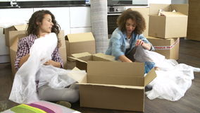 Two Women Moving Into New Home And Unpacking Boxes. Two women unpacking breakables into cardboard box ready for move. Shot on Sony FS700 in PAL format at a frame stock video