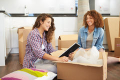 Two Women Moving Into New Home And Unpacking Boxes. Two Happy Women Moving Into New Home And Unpacking Boxes In Kitchen royalty free stock photography
