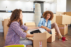 Two Women Moving Into New Home And Unpacking Boxes. Sitting On Kitchen Floor stock photos