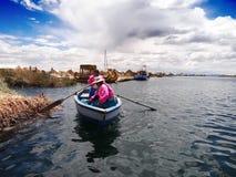 Two women navigating Lake Titicaca. Puno, Peru – September 20, 2011: Two indigenous Uros indian women with pink jackets navigating Lake Titicaca, at 12,507 Royalty Free Stock Image