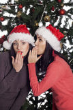 Two women near christmas tree gossip Royalty Free Stock Photo