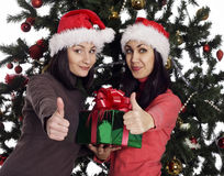 Two women near christmas tree with present showing hand ok sign Stock Photos