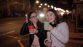 Two women on a night city walk are at the bus stop, drink coffee and have fun talking stock video