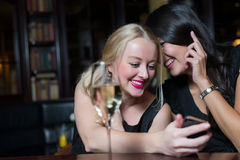 Two women friends on a night out using mobile phon. Two beautiful young women friends enjoying a glass of wine on a night out using their mobile phones laughing Royalty Free Stock Image