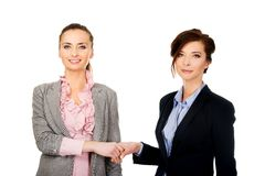Two women in office outfits giving handshake. Royalty Free Stock Photo