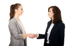 Two women in office outfits giving handshake. Stock Photography