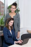 Two women in the office. A young business women with headset is typing at a notebook. Another women is standing behind her and is smiling to the camera Royalty Free Stock Photos