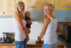 Two women and one baby at kitchen Royalty Free Stock Images