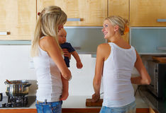 Two women and one baby at kitchen Royalty Free Stock Image