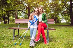 Two women, one healthy and one with a sprained foot, on a bench stock photos