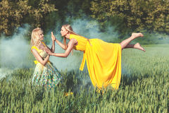 Two women, one levitates. Royalty Free Stock Image