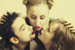 Two women and one man with the red ripe cherries Stock Photos