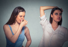 Two women, one pinching nose something stinks, girls underarm. Isolated gray background royalty free stock photography