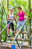 Two women, one pregnant, at fitness sport in climbing park stock images