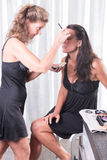 Two women, one is putting the other make up on.  Royalty Free Stock Photography