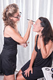 Two women, one is putting the other make up on.  Royalty Free Stock Photos