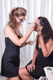 Two women, one is putting the other make up on.  Stock Images