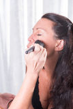 Two women, one is putting the other make up on.  Royalty Free Stock Image