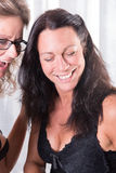 Two women, one is putting the other make up on. They are laughing Royalty Free Stock Image