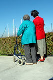 Two women one with a walker. Two women on a walk royalty free stock photos