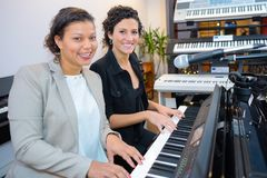 Two women at organ keyboard stock photography