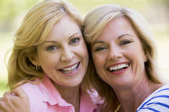 Two women outdoors embracing and smiling. At camera Royalty Free Stock Images