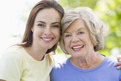 Two women outdoors embracing and smiling Stock Photos