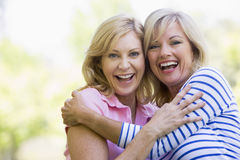 Two women outdoors hugging and smiling royalty free stock images