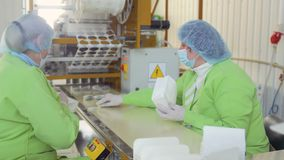 Two women packing tea bags in package at tea factory. Two workers are packing tea bags inside the paper bag for sale. Conveyor belt automatically moves tea bags stock video footage