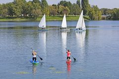 Two women on paddle board and three boat sailling. In lake Royalty Free Stock Photos