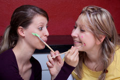 Two women paint each other's face Royalty Free Stock Photo