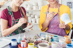 Two women painting own ceramic tableware in DIY workshop. With brushes stock photos