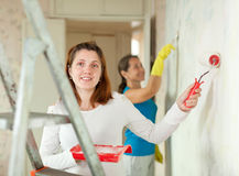 Two women paints wall stock photos