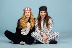 Two women in pajamas sit on floor on a blue background. Studio shoot stock photos