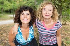 Two women in park after running jogging. In summer stock photography